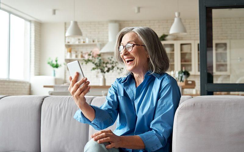 Starsza, śmiejąca się kobieta z telefonem