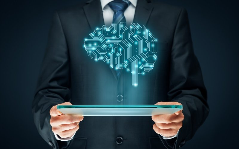 Grafika komputerowa - człowiek trzyma tablet, nad którym unosi się renderowany mózg