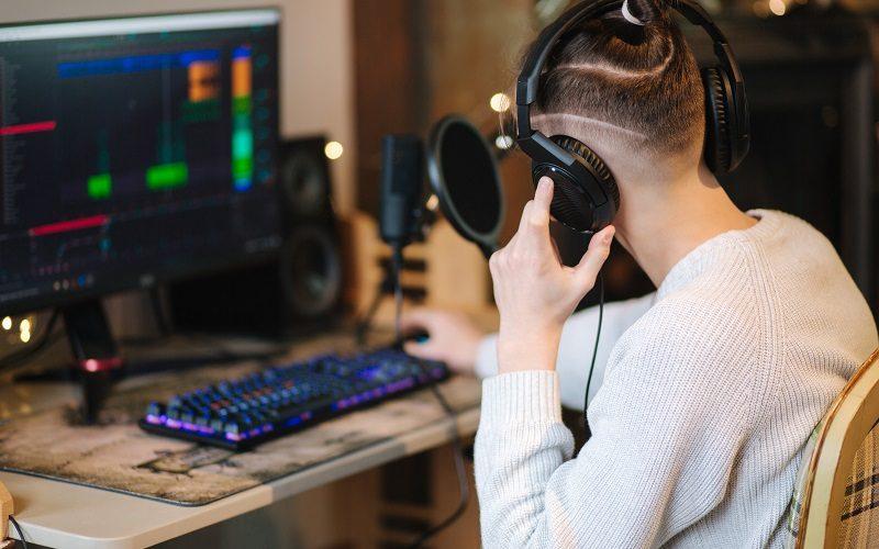 Młody mężczyzna siedzący przed stanowiskiem do nagrywania podcastów (klawiatura, monitor, mikrofon, słuchawki)